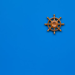 Copper yacht steering wheel on blue background. Symbol of leadership. Copy space.