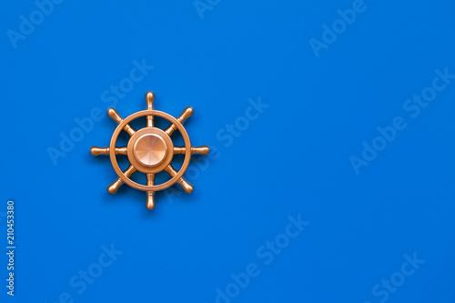 Copper Yacht Steering Wheel On Blue Background Symbol Of Leadership
