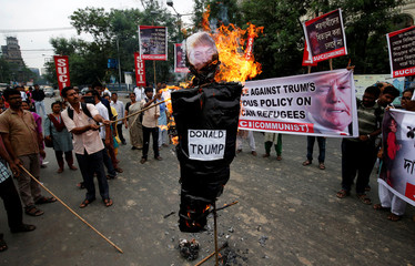 Activists from the Socialist Unity Centre of India (SUCI) burn an effigy depicting U.S. President Donald Trump during a protest in Kolkata