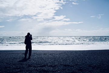 A solitary photographer was taking sea view photo at shiny black sand beach