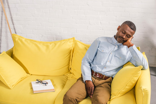 senior african american man sleeping on couch, book and eyeglasses on sofa