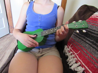 Unrecognizable woman relaxing on a couch playing the ukulele