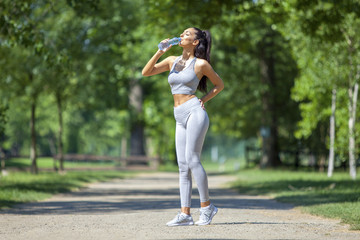 Young fit beautiful girl resting and drinking water