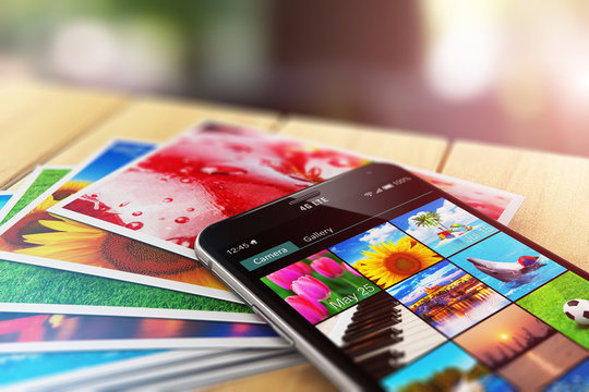 Stack of photos and smartphone with image gallery app
