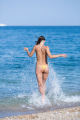 Tall slim tanned female person rushes into the sea