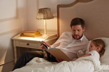 Young man with book lying by his cute little daughter and reading tales before sleep