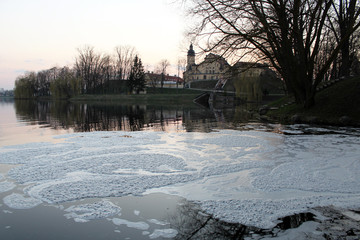 Photo of the castle at sunset, foam, reflection in the lake.