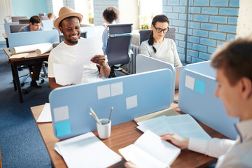 Happy young African-american businessman in hat and t-shirt sitting by individual workplace in open space office and reading paper among colleagues