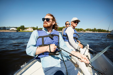 Fototapeten Motorisierter Wassersport Group of men in protective lifejackets and sunglasses floating on yacht or motor boat on summer day