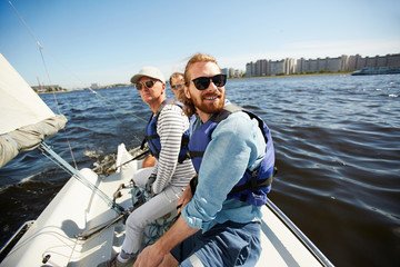 Deurstickers Zeilen Active men in sunglasses sitting on yacht while floating in lake on hot summer day