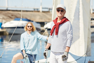 Senior man and his assistant in sunglasses working on yacht while preparing for new sailing season