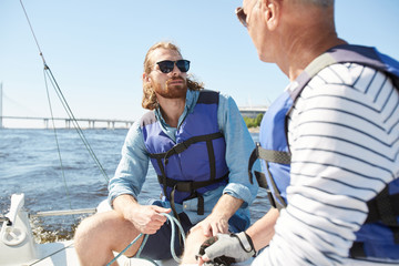Young and senior active men in lifejackets sailing on yacht and talking on hot summer day