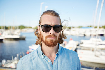 Bearded man in sunglasses and denim shirt standing in front of camera with yachts on background