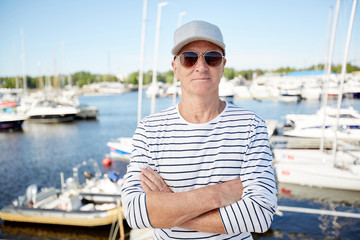 Senior cross-armed yachtsman in sunglasses and striped singlet standing in front of camera
