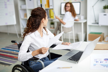 Young economist in wheelchair working with papers by workplace and consulting with colleague
