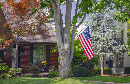 Brick house set in traditional neighborhood with large trees a bird feeder and colorful flowers and an American flag