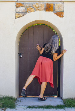 Woman with long grey hair peeks around locked arched door in wall to garden beyond