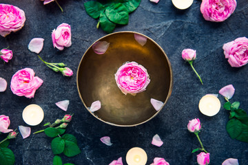 Tibetan singing bowl with floating rose inside. Burning candles, tea rose flowers and petals on the black stone background. Meditation and Relax. Exotic massage, spa procedure. Selective focus.