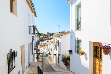 Narrow street with houses in picturesque white village of Mijas, Andalusia, Spain