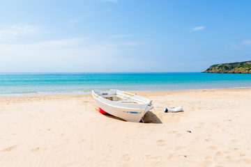 White fishing boat on white sand Bolonia beach and blue sea view, Andalusia, Spain