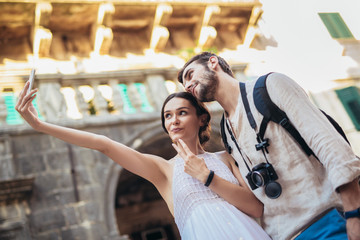 Young couple taking a selfportrait with smartphone. People traveling