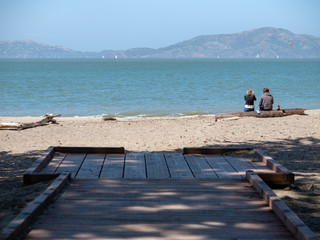 Platform leading to the back with a couple sitting on a log and enjoying the view of the San Francisco Bay