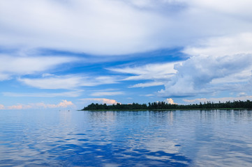 Blue sky with Cumulus clouds over the forest at the Lake Ladoga shore