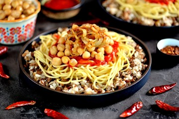 Kushari or Koushari - Egyptian dish of lentils, rice, pasta, chickpeas with tomato sauce and crispy onions. Arabic cuisine