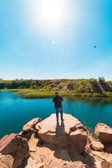 guy tourist on a cliff face looking at a pond, tourism, vacation, travel, summer vacation