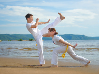 A woman and a boy to train capoeira on the beach