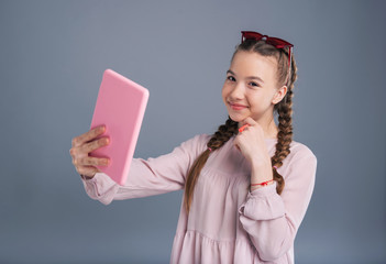 Selfie lover. Pretty teenage girl holding a pink tablet and taking a selfie with it while posing isolated on a blue-grey background