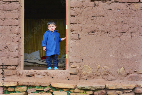 sad little latin boy in old adobe house concept of poverty stock