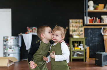 Little brother kissing his pretty sister in a creative class.