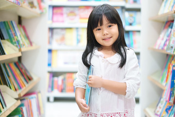 Asian children or kid girl happy smile and shopping or choose tale or story book on bookshelf in bookstore or library room at kindergarten school or nursery for learning and studying with education