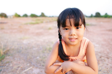 Asian children cute poor or kid girl smile with happy fun because come back home to country and wear traditional top or sleeveless shirt sit on arid soil or ground for agriculture at countryside