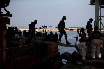 Migrants leave a rescue boat upon arrival at the port of Malaga