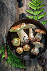 Top view of tasty boletus and onion on the pan