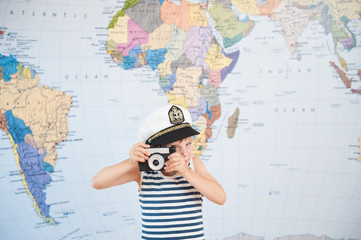 funny little boy in captain hat taking picture by old retro film camera near map