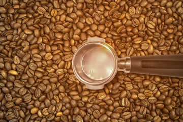 Metal espresso machine empty scoop on roasted coffee beans background