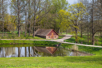 Country scene of stone barn close the lake. Summer daytime