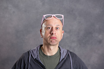 man with pink glasses looking amazed in to the camera