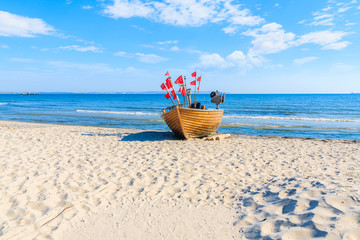 Traditional wooden fishing boat on sandy beach in Binz summer resort, Ruegen island, Baltic Sea,...