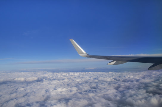 View from airplane window with silver wing, blue sky, white clouds and horizon; Flight above the clouds