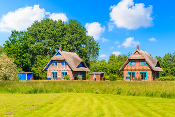 Wall Mural - Traditional thatched roof house on green meadow in Gross Zicker village on sunny summer day, Ruegen island, Baltic Sea, Germany