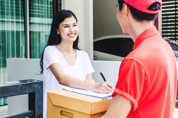 Woman putting signature in clipboard on cardboard box to receiving package with delivery man in red uniform.courier service concept