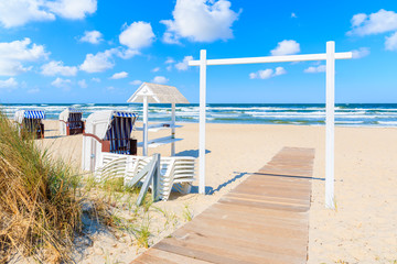 Entrance gate to sandy beach with traditional wooden chairs on beautiful day with sunny sky and white clouds in Baabe village, Ruegen island, Baltic Sea, Germany