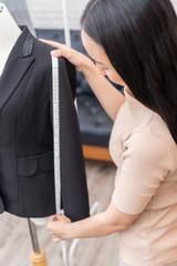 Female fashion tailor is measuring office suit jacket