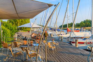 SEEDORF PORT, RUEGEN ISLAND - JUN 1, 2018: Tourists relaxing in restaurant at lake pier in Seedorf sailing port, Baltic Sea, Germany. Ruegen is popular tourist destination in summer season.