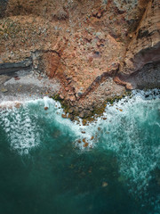 Aerial top view of sea waves hitting rocks on the beach with turquoise sea water. Amazing rock cliff seascape in the Portuguese coastline.