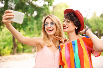 Young women in stylish clothes taking selfie outdoors